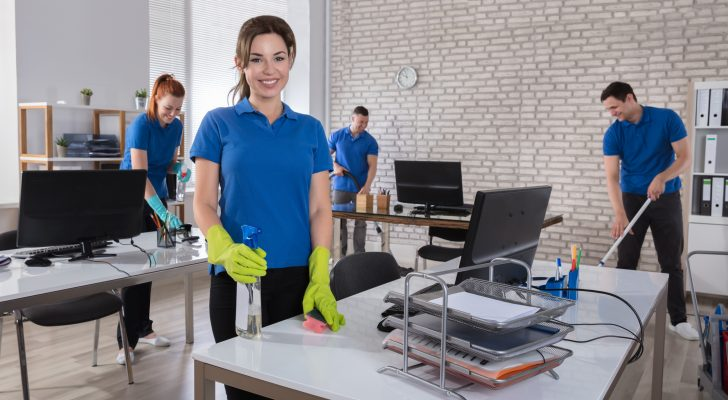 Portrait Of A Happy Female Janitor With Cleaning Equipments In Office